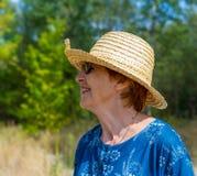 Porträt einer lächelnden Frau in einem Strohhut und in der Sonnenbrille Lizenzfreies Stockfoto