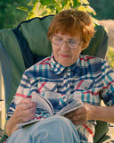 Porträt einer lächelnden Frau mit Gläsern und Blätterbildungsbuch Stockfotografie