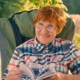 Porträt einer lächelnden Frau mit Gläsern und Blätterbildungsbuch Lizenzfreies Stockbild