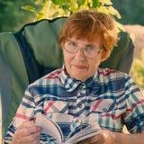 Porträt einer lächelnden Frau mit Gläsern und Blätterbildungsbuch Lizenzfreie Stockfotos