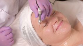 Porträt einer lächelnden Frau von mittlerem Alter auf einem Verfahren in einem Schönheitssalon Hardware Cosmetology Ein Kosmetike stock video footage