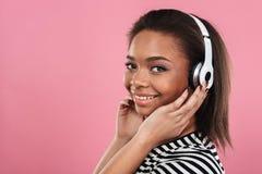 Porträt einer lächelnden glücklichen afroen-amerikanisch Frau in den Kopfhörern stockfotos