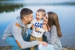 Porträt einer lächelnden jungen Familie nahe einem See stockfotos