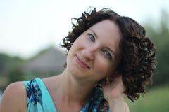 Porträt einer lächelnden jungen Frau mit dem dunklen gelockten kurzen Haar Stockfotos