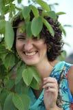 Porträt einer lächelnden jungen Frau mit dem dunklen gelockten kurzen Haar Stockbild