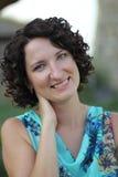 Porträt einer lächelnden jungen Frau mit dem dunklen gelockten kurzen Haar Lizenzfreies Stockbild