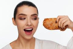 Porträt einer lächelnden Schönheit mit einem Brötchen des indischen Sesams in ihrer Hand lizenzfreie stockfotos