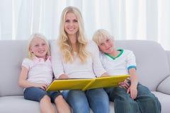 Porträt einer Mutter, die ein Geschichtenbuch mit Kindern hält Stockbilder