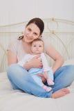 Porträt einer Mutter und des Babys im Schlafzimmer stockfotografie