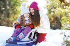 Porträt einer Mutter und des Kindes im Schlitten, der Spaß, sonnigen Winter hat Stockfotos