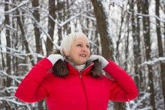 Porträt einer netten älteren Frau im Winterschneeholz im roten Mantel Stockbild