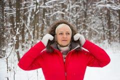 Porträt einer netten älteren Frau im Winterschneeholz im roten Mantel Stockbilder