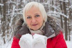 Porträt einer netten älteren Frau im Winterschneeholz im roten Mantel Stockfotografie