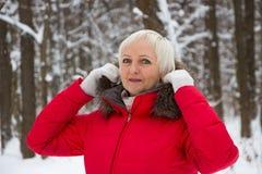 Porträt einer netten älteren Frau im Winterschneeholz im roten Mantel Lizenzfreie Stockfotografie