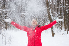 Porträt einer netten älteren Frau im Winterschneeholz im roten Mantel Lizenzfreie Stockfotos