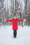 Porträt einer netten älteren Frau im Winterschneeholz im roten Mantel Stockfotos