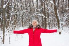 Porträt einer netten älteren Frau im Winterschneeholz im roten Mantel Stockfoto