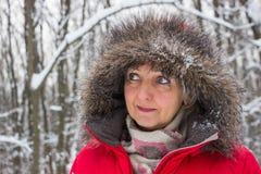 Porträt einer netten älteren Frau im Winterschneeholz im roten Mantel lizenzfreie stockbilder