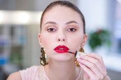 Porträt einer netten attraktiven Frau, die auf Lippenstift sich setzt stockbild
