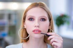 Porträt einer netten attraktiven Frau, die rosa Lippenstift anwendet lizenzfreie stockfotos