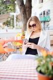 Porträt einer netten blonden Frau las etwas an ihrem intelligenten Telefon beim Sitzen in der modernen Kaffeestube, schöner junge stockfotos