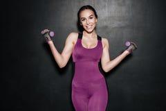 Porträt einer netten lächelnden Eignungsfrau, die Übungen tut Lizenzfreies Stockbild