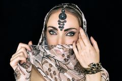 Porträt einer orientalischen jungen Frau in einem Schal mit einer Verzierung und Juwelen auf einem schwarzen Hintergrund lizenzfreie stockbilder