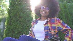 Porträt einer positiven lächelnden jungen Afroamerikanerfrau sperrte in einem Rollstuhl, der die Kamera auf einem sonnigen betrac stock footage