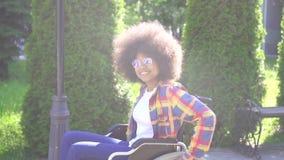 Porträt einer positiven lächelnden jungen Afroamerikanerfrau sperrte in einem Rollstuhl, der die Kamera betrachtet stock footage