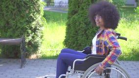 Porträt einer positiven lächelnden jungen Afroamerikanerfrau sperrte in einem Rollstuhl, der im Park an einem sonnigen Tag im Fre stock footage