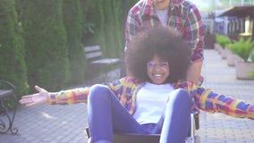 Porträt einer positiven lächelnden jungen Afroamerikanerfrau sperrte in einem Rollstuhl und ihr Freund freut sich und hebt an stock footage