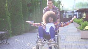 Porträt einer positiven lächelnden jungen Afroamerikanerfrau sperrte in einem Rollstuhl und ihr Freund freut sich und hebt an stock video footage