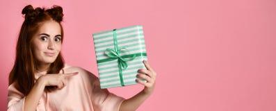 Porträt einer recht lächelnden Rothaarigemädchenholdinggeschenkbox und -c$betrachtens sie, lokalisiert über Farbrosa Hintergrund lizenzfreies stockbild