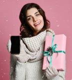 Porträt einer recht zufälligen Mädchenholdinggeschenkbox und -c$zeigens des Handys des leeren Bildschirms lizenzfreies stockfoto