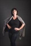 3/4 Porträt einer reifen dunkelhaarigen Frau mit den Händen auf Hüften Lo Lizenzfreie Stockfotografie