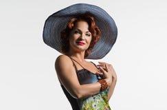 Porträt einer reifen Frau mit dem roten Haar und einem Hut Stockbild