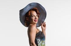 Porträt einer reifen Frau mit dem roten Haar und einem Hut Stockfotografie
