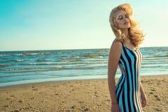 Porträt einer reizend blonden langhaarigen Frau im langen gestreiften Schwarzweiss-Kleid, das Aroma des Meeres riecht und genießt stockfotos