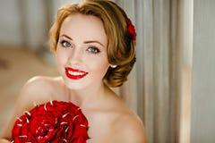 Porträt einer reizend Mädchenblondine mit schönem Lächeln und Rot Lizenzfreie Stockfotografie