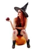 Porträt einer reizend rothaarigen Hexe, die Kürbis mit Rot hält Stockfotos
