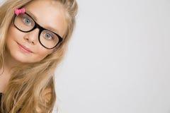 Porträt einer reizenden Tochter des kleinen Mädchens im langen blonden Haar und in den schwarzen Gläsern mit rosa Bogen Lizenzfreie Stockbilder