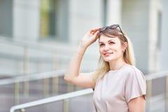 Porträt einer romantischen Frau mit Sonnenbrille, die herzlichst an einem sonnigen Tag im Frühjahr lächelt stockfotografie