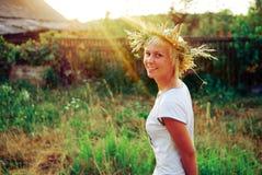 Porträt einer romantischen lächelnden jungen Frau in einem Circlet von Blumen draußen Lizenzfreie Stockfotografie