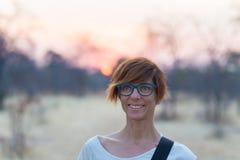 Porträt einer roten behaarten Frau mit grünen Augen, Brillen und lächelndem Gesichtsausdruck Sonnenuntergang am Horizont Geschoss Stockbild