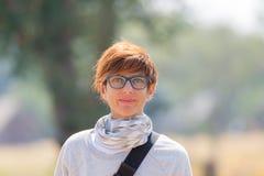 Porträt einer roten behaarten Frau mit grünen Augen, Brillen und lächelndem Gesichtsausdruck Sonnenuntergang am Horizont Geschoss Lizenzfreie Stockfotografie
