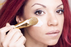 Porträt einer Rothaarigeschönheit, die Feuchtigkeitscreme auf ihrer Haut anwendet Stockfotografie