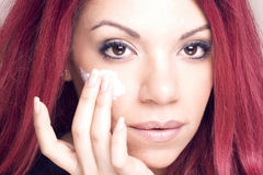 Porträt einer Rothaarigeschönheit, die Feuchtigkeitscreme auf ihrer Haut anwendet stockbild