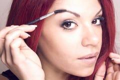 Porträt einer Rothaarigeschönheit mit einem Augenbrauenbürstenwerkzeug Lizenzfreies Stockbild