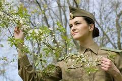 Porträt einer russischen Militärfrau in einem blühenden Garten lizenzfreie stockbilder