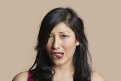 Porträt einer schönen beißenden Lippe der jungen Frau über farbigem Hintergrund Lizenzfreie Stockbilder